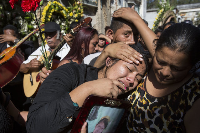 In this March 17, 2017 file photo, Shirley Palencia weeps during the burial service for 17-year-old sister Kimberly Palencia Ortiz, who died in the Virgen de la Asunción Safe Home fire, at the cemetery in Guatemala City. Authorities said the fire that swept through parts of the institution when mattresses were set ablaze during a protest by girls protesting conditions at the overcrowded youth shelter. (Photo by Moises Castillo/AP Photo)