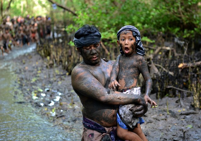 Balinese man holds his son after putting mud on their body during a mud bath tradition known as Mebuug-buugan, in Kedonganan village, near Denpasar on Indonesia's resort island of Bali on March 29, 2017. The Mebuug-buugan is held a day after Nyepi aimed at neutralizing bad traits. (Photo by Sonny Tumbelaka/AFP Photo)