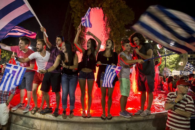 """No"" supporters celebrate referendum results on a street in central in Athens, Greece July 5, 2015. Greeks voted overwhelmingly ""No"" on Sunday in a historic bailout referendum, partial results showed, defying warnings from across Europe that rejecting new austerity terms for fresh financial aid would set their country on a path out of the euro. (Photo by Marko Djurica/Reuters)"