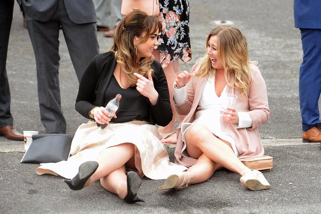 After a long day of race watching – two friends give their feet a rest during the Grand National Festival at Aintree Racecourse on April 6, 2017 in Liverpool, England. (Photo by Mercury Press)