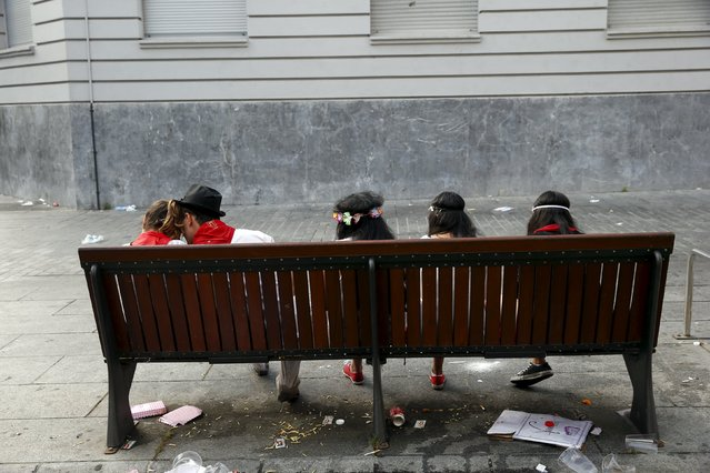 Revellers rest on a bench after the first running of the bulls of the San Fermin festival in Pamplona, northern Spain, July 7, 2015. (Photo by Susana Vera/Reuters)
