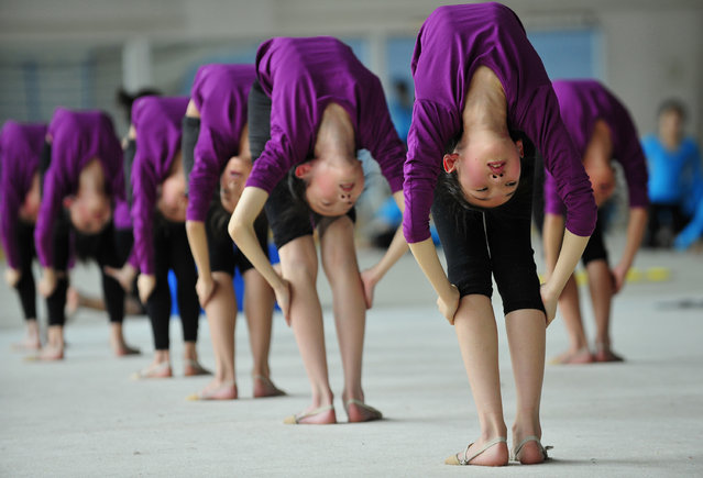 Students stretch during a training session at a gymnastic course at Shenyang Sports School in Shenyang, Liaoning province May 9, 2012. Some 60 students, between the ages of 6 to 15, undergo a nine-year gymnastic programme which includes foundation courses and gymnastic training courses at Shenyang Sports School, and those who are outstanding may be selected to join the national team, according to local media. (Photo by Reuters/Stringer)