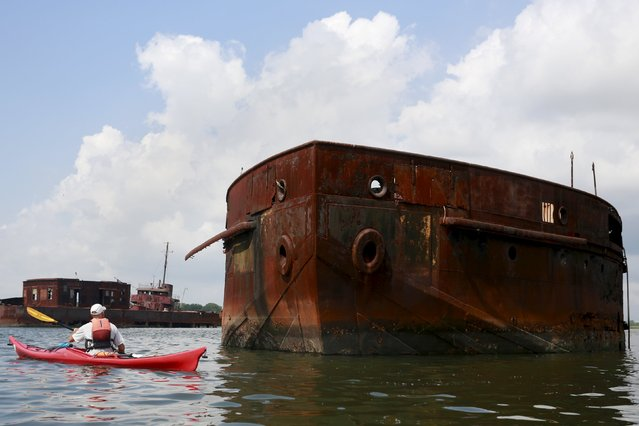 "John Pagani, owner of Kayak East, paddles by a vessel during the ""Graveyard of Ships"" kayak tour on the Arthur Kill, New York, July 7, 2015. (Photo by Shannon Stapleton/Reuters)"