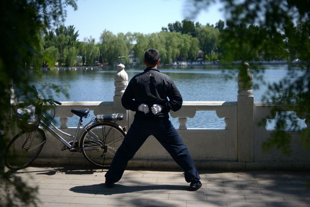 A man exercises at the lakeside in a park in Beijing on May 5, 2014. China's manufacturing sector contracted for a fourth consecutive month in April, HSBC said on May 5, the latest sign that the world's second-largest economy is slowing. (Photo by Wang Zhao/AFP Photo)