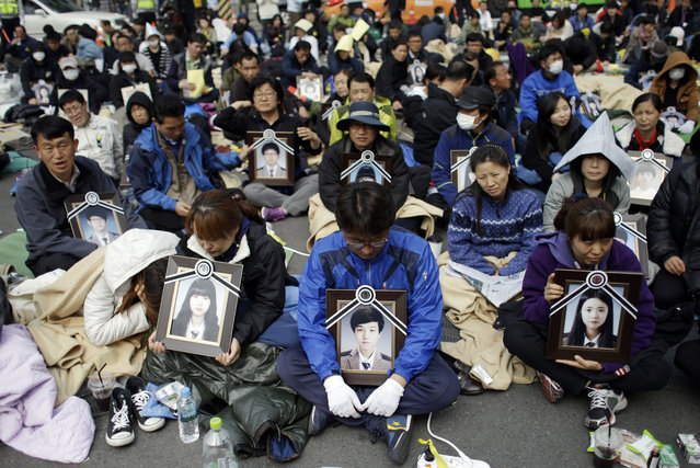 Family members holding the portraits of the victims of the sunken ferry Sewol, sit on a street near the presidential Blue House in Seoul, South Korea, Friday, May 9, 2014. (Photo by Lee Jin-man/AP Photo)