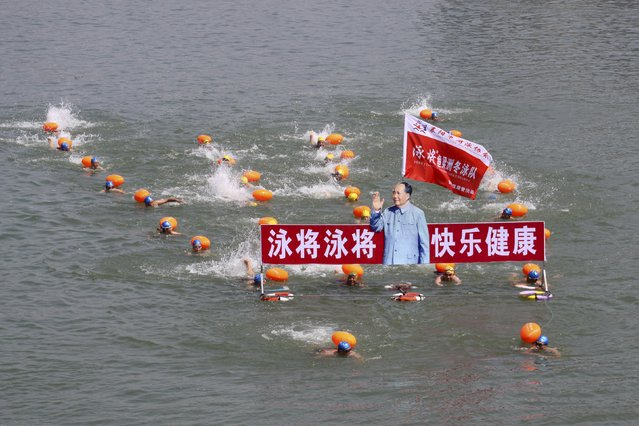 "Participants swim with a portrait of late Chinese Chairman Mao Zedong in the Hanjiang River, a large branch of the Yangtze River in Xiangyang, Hubei province July 12, 2015. Hundreds of residents took part in the event to celebrate the upcoming 49th anniversary of Mao swimming in the Yangtze River on July 16, 1966, local media reported.  The words beside the portrait read, ""Swimming champions, be happy and healthy"". (Photo by Reuters/Stringer)"