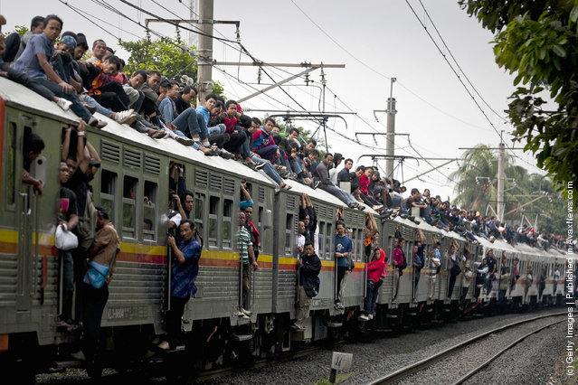 Commuters ride on the roof of a Jakarta state rail train at Cawang train station in Jakarta, Indonesia