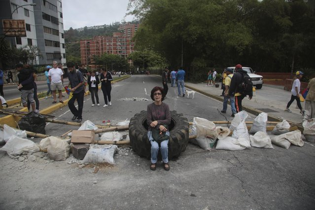 A woman rests on a tire at a roadblock set up by residents outside her home in El Hatillo's municipality near Caracas, Venezuela, Tuesday, May 2, 2017. (Photo by Fernando Llano/AP Photo)