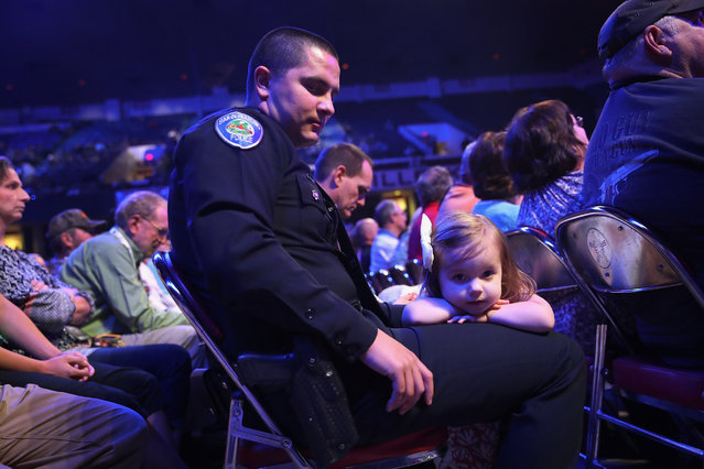 Emilia Pesquera rests on the lap of  her father Marcus as he listens to speakers at the National Rifle Association's NRA-ILA Leadership Forum during the NRA Convention at the Kentucky Exposition Center on May 20, 2016 in Louisville, Kentucky. Marcus Pesquera was chosen by the NRA as the officer of the year. The convention, which opened today, runs until May 22. (Photo by Scott Olson/Getty Images)