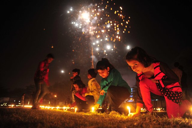 Young kids light candle during pujan at a stadium on the occasion of Dhanteras festival in Allahabad, India on October 28, 2016. Dhana Trayodashi is the first day of the Indian Diwali and Nepalese Tihar Festival. (Photo by Prabhat Kumar Verma/Pacific Press/LightRocket via Getty Images)