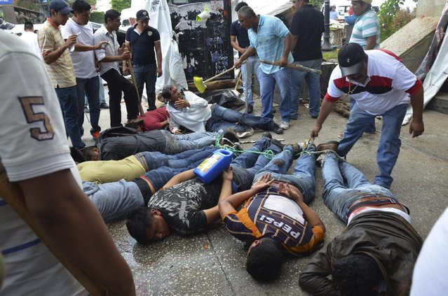 Captured men lie face down and tied up after  rival taxi unions fighting for permits clashed in the city of Chilpancingo, Mexico, Monday, July 20, 2015. (Photo by Alejandrino Gonzalez/AP Photo)