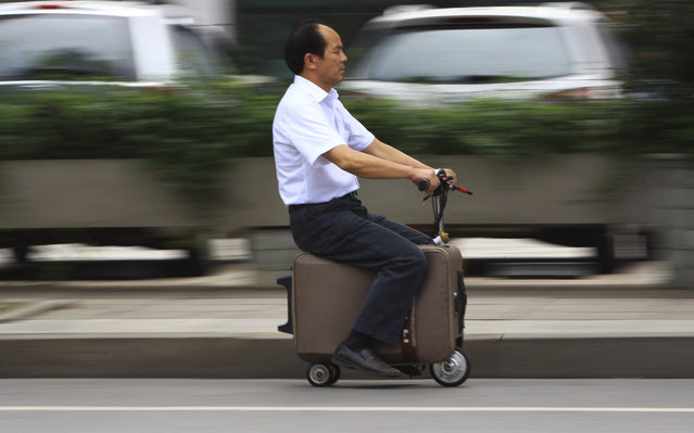 He Liang rides his homemade suitcase vehicle along a street in Changsha, Hunan province, China, on May 28, 2014. He spent 10 years modifying the suitcase into a motor-driven vehicle. The suitcase has a top speed of up to 20km/h and the power capacity to travel up to 50-60km after one charge, according to local media. (Reuters/China Daily)