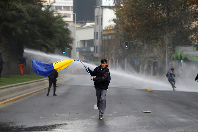 A demonstrator waves a flag as they clash with riot police during an unauthorized march called by secondary students to protest against government education reforms in Santiago, Chile, May 26, 2016. (Photo by Ivan Alvarado/Reuters)