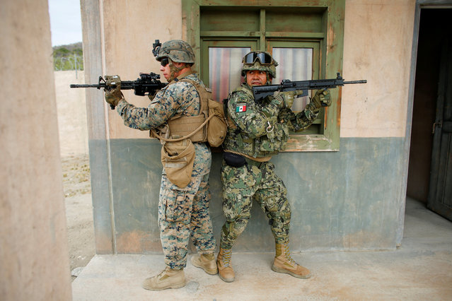 U.S. Marine Jacob Kostelecky (L) keeps watch with a Mexican Marine during operations in urban terrain as they train side-by-side during a Rim of the Pacific Exercise (RIMPAC) at Camp Pendleton, California, U.S. July 9, 2018. (Photo by Mike Blake/Reuters)