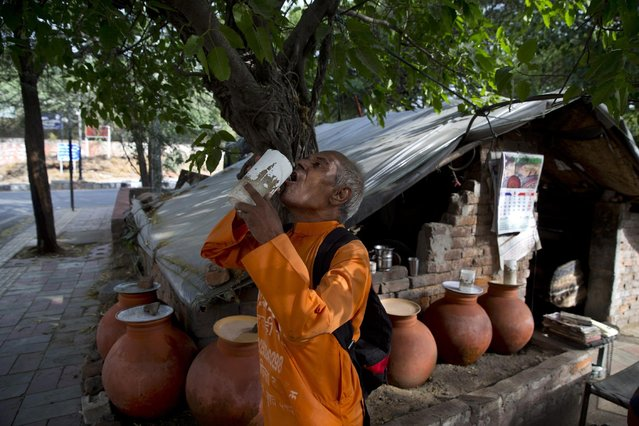 """In this June 11, 2015 photo, Omkarnath, who goes by the name """"Medicine Baba"""",  drinks water after spending an hour shouting out to people to donate unused medicines, in New Delhi, India. (Photo by Saurabh Das/AP Photo)"""
