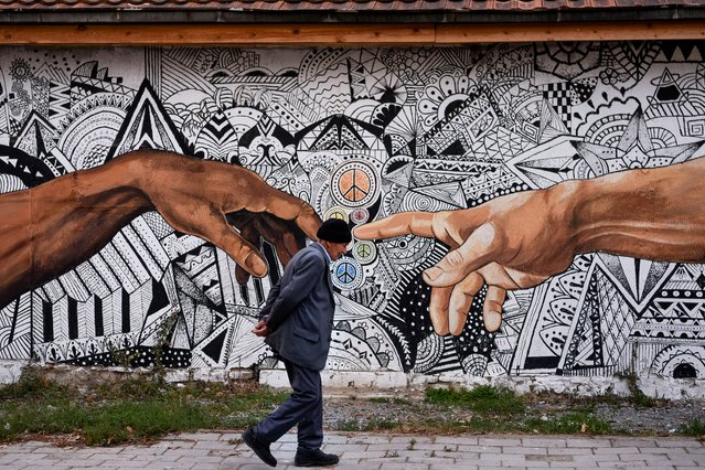 A pedestrian walks past a mural artwork painted on the wall of a house in the town of Ferizaj, Kosovo on November 3, 2019. (Photo by Armend Nimani/AFP Photo)