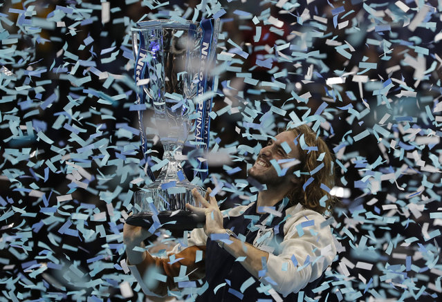 Stefanos Tsitsipas of Greece holds up the trophy and celebrates as confetti falls after defeating Austria's Dominic Thiem in the final of the ATP World Finals tennis match at the O2 arena in London, Sunday, November 17, 2019. (Photo by Kirsty Wigglesworth/AP Photo)