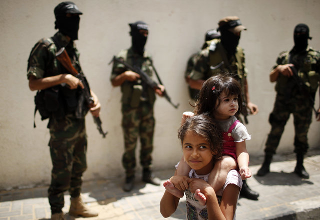 A Palestinian girl carries her sister as they pass militants during the funeral of militant Mohammed Al-Awor in Beit Lahiya in the northern Gaza Strip June 12, 2014. (Photo by Mohammed Salem/Reuters)