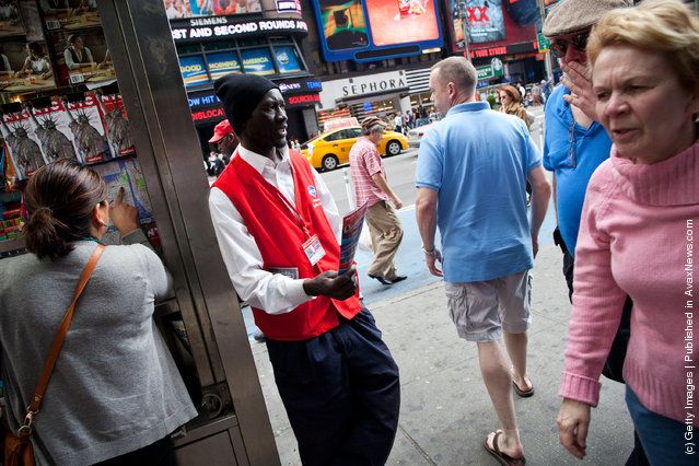 A Grayline bus tours worker hands out flyers to people in Times Square