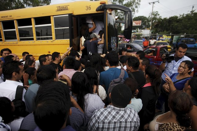 People try to board a goverment bus during the second day of a suspension of public transport services in Apopa, El Salvador July 28, 2015. (Photo by Jose Cabezas/Reuters)
