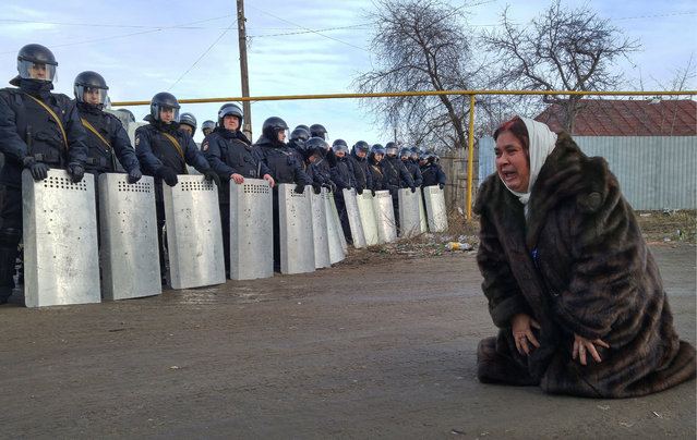 Local resident and law enforcement officers during the riots in the village of Plekhanovo in Tula region, Russia on March 17, 2016. On the eve of a group of residents of the village, where mainly representatives of gypsy ethnicity live, tried to prevent the gas service from repairing the pipeline damaged by an unauthorized attempt to connect to the gas supply system. Repair work had to be suspended until the arrival of the police. (Photo by Sergey Starikov/TASS)