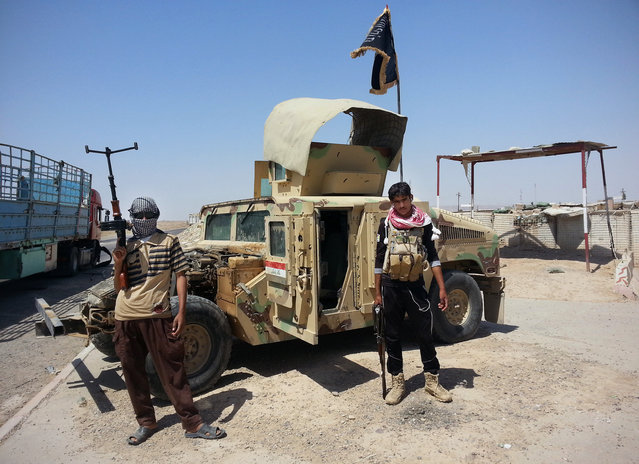 Al-Qaeda inspired militants stand with captured Iraqi Army Humvee at a checkpoint outside Beiji refinery, some 250 kilometers (155 miles) north of Baghdad, Iraq, Thursday, June 19, 2014. The fighting at Beiji comes as Iraq has asked the U.S. for airstrikes targeting the militants from the Islamic State of Iraq and the Levant. (Photo by AP Photo)