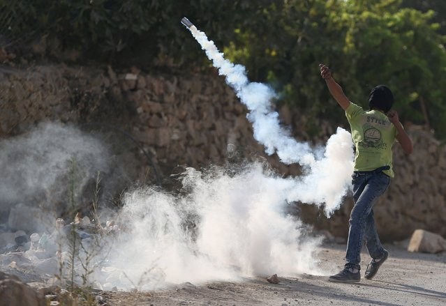 A Palestinian protester returns a tear gas canister fired by Israeli troops during clashes following the funeral of Palestinian youth Laith al-Khaldi, in Jalazoun refugee camp near the West Bank city of Ramallah August 1, 2015. Al-Khaldi died on Saturday at a West Bank hospital following a clash with Israeli troops near Ramallah, Palestinian hospital officials said. (Photo by Mohamad Torokman/Reuters)