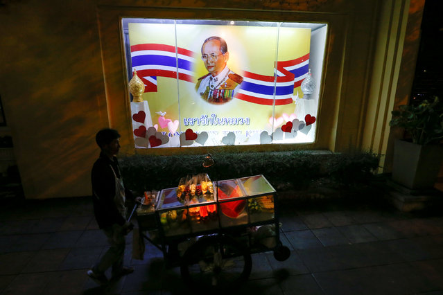 A man pushes a cart with fruits as he walks in front of a painting of Thailand's King Bhumibol Adulyadej in Bangkok, Thailand, June 6, 2016. (Photo by Jorge Silva/Reuters)