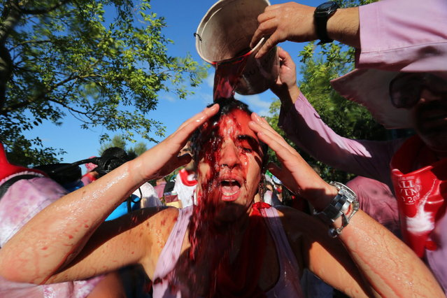 """Revelers pour wine on each other as they take part in the """"Battle of Wine"""" (La batalla del vino de Haro), a wine fight, during the Haro Wine Festival, in Haro, in the northern province of La Rioja on June 29, 2014. More than nine thousand locals and tourists threw around 130.000 litres of wine at each other during the Haro Wine Festival, according to local media. (Photo by Cesar Manso/AFP Photo)"""