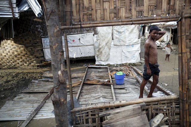 Rohingya children are pictured through a damaged shelter in Rohingya IDP camp outside Sittwe, Rakhine state August 4, 2015. (Photo by Soe Zeya Tun/Reuters)