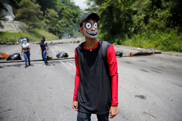 A protester wears a mask while he stands in front of a roadblock during a rally against Venezuela's President Nicolas Maduro's government in Caracas, Venezuela June 26, 2017. (Photo by Ivan Alvarado/Reuters)