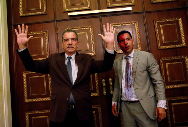 Opposition lawmaker Luis Stefanelli gestures next to fellow opposition lawmaker Leonardo Regnault after a group of government supporters burst into Venezuela's opposition-controlled National Assembly during a session, in Caracas, Venezuela on July 5. 2017. (Photo by Carlos Garcia Rawlins/Reuters)