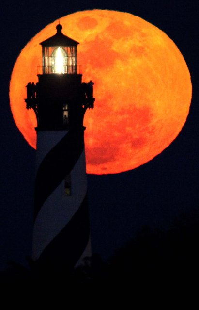 A group of sightseers watch the the moon rise from the top of the St. Augustine Lighthouse during the annual Lighthouse Festival in St. Augustine, Florida