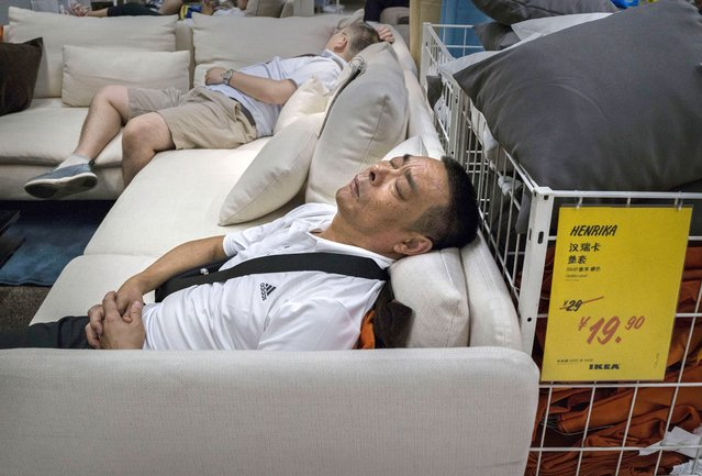 Chinese shoppers sleep on a sofa in the showroom of the IKEA store on July 6, 2014 in Beijing, China. Of the world's ten biggest Ikea stores, 8 of them are in China to cater to the country's growing middle class. The stores are designed with extra room displays given the tendency for customers to make a visit an all-day affair. Store management does not discourage shoppers from sleeping on Ikea furniture, even marking them with signs inviting customers to try them out. (Photo by Kevin Frayer/Getty Images)