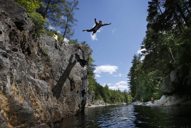 Russell Keene, 52, of Livermore Falls, Maine, does a swan dive into the Swift River off a cliff at Coos Canyon in Byron, Maine. The canyon is considered one of the premier swimming holes in the U.S. (Photo by Robert F. Bukaty/AP Photo)