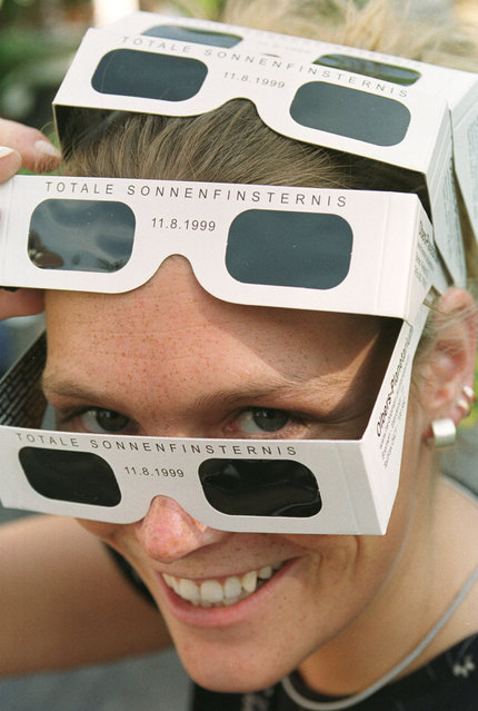 Stefanie Otten poses with pairs of safety goggles in Bremen, northwest Germany, Tuesday, July 20, 1999. Astronomers expect a total solar eclipse on Wednesday, July 11, 1999. Experts emphasize: never look directly into the sunlight. Especially not through binoculars, cameras or other optical instruments. They focus the light into the eyes and this could lead to blindness. (Photo by Joerg Sarbach/AP Photo)