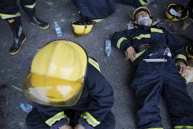 Firefighters take a break after trying to put fire down at the explosion site in Binhai new district in Tianjin, China August 13, 2015. (Photo by Damir Sagolj/Reuters)