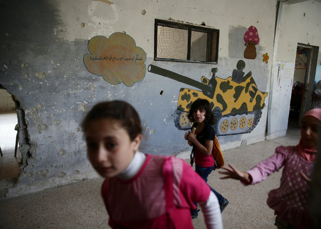 """Girls walk through a damaged corridor inside a school in the town of Douma, eastern Ghouta in Damascus, Syria May 24, 2016. The writing reads in Arabic, """" Your shelling will not let the creativity in our hearts and minds die"""". (Photo by Bassam Khabieh/Reuters)"""