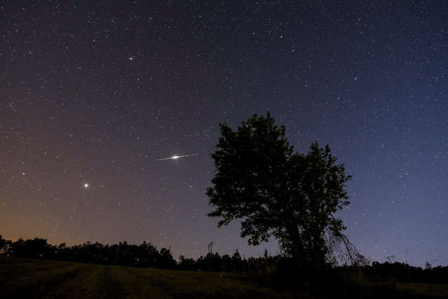 An iridium satellite's flash (C-L) is seen on the summer night sky from the vicinity of Repashuta, some 170km northeast of Budapest, Hungary, late 15 June 2017. (Photo by Peter Komka/EPA)