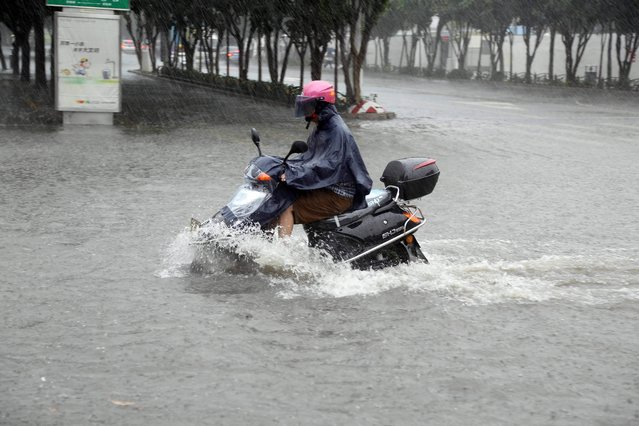 A motorcyclist rides through a flooded area in Jinjiang, south China's Fujian province of July 23, 2014 as typhoon Matmo makes landfall in China. Typhoon Matmo pounded Taiwan with fierce winds and downpours, leaving nine people injured, shuttering financial markets, and interrupting rail and air transportation. (Photo by AFP Photo)