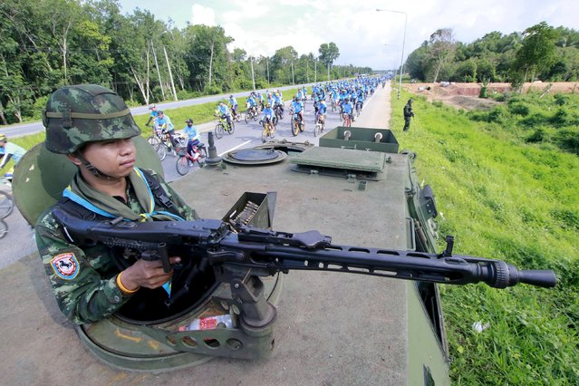 """A soldier mans the weapon on his vehicle as people take part in the """"Bike for Mom"""" event in the troubled southern province of Yala, Thailand, August 16, 2015. (Photo by Athit Perawongmetha/Reuters)"""