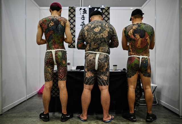 Three men display their tattoos during the International Malaysia Tattoo Expo in Kuala Lumpur on November 29, 2019. The international tattoo expo is held for the first ime in Kuala Lumpur celebrating that art of tattoo and gathering over a hundred tattoo artists from 40 countries. (Photo by Mohd Rasfan/AFP Photo)