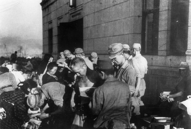 In this August 6, 1945, file photo, shortly after the first atomic bomb ever used in warfare was dropped by the United States over the Japanese city of Hiroshima, survivors are seen as they receive emergency treatment by military medics. (Photo by AP Photo)