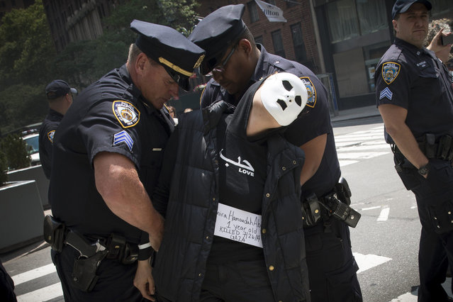 An activist shouts slogans as she is detained by New York City Police for blocking traffic during a protest in Midtown, Manhattan, in New York, July 31, 2014. About two dozen protesters, who identified themselves as members of the arts and activism collective, wore black clothing and white masks as they marched to protest against Israel's military action in the Gaza strip. (Photo by Mike Segar/Reuters)