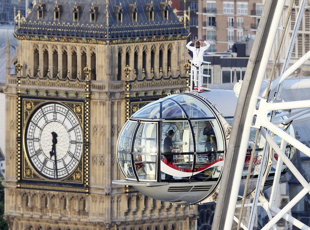 British athlete Mo Farah stands atop of a pod on the London Eye, with Big Ben's clock tower in background, as he bids a final farewell to British track competitive athletics after winning gold in the 10,000m and silver in the 5,000m at the IAAF World Championships in London, Sunday August 13, 2017. Farah is due to retire from the track at the end of the month, after the Diamond League in Zurich, and hopes to focus on the marathon distance. (Photo by Jonathan Brady/PA Wire via AP Photo)