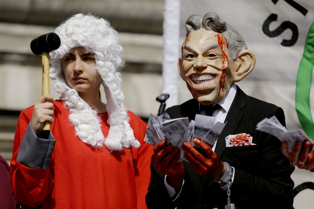 A protester wearing a former British Prime Minister Tony Blair mask, right, and another dressed as a judge pose for the media on a stage outside the Queen Elizabeth II Conference Centre in London, shortly before the publication of the Chilcot report into the Iraq war, Wednesday, July 6, 2016. Thirteen years after British troops marched into Iraq and seven years after they left a country that's still mired in violence, a mammoth official report is about to address the lingering question: What went wrong? On Wednesday, retired civil servant John Chilcot will publish his long-delayed, 2.6 million-word report on the divisive war and its chaotic aftermath. (Photo by Matt Dunham/AP Photo)