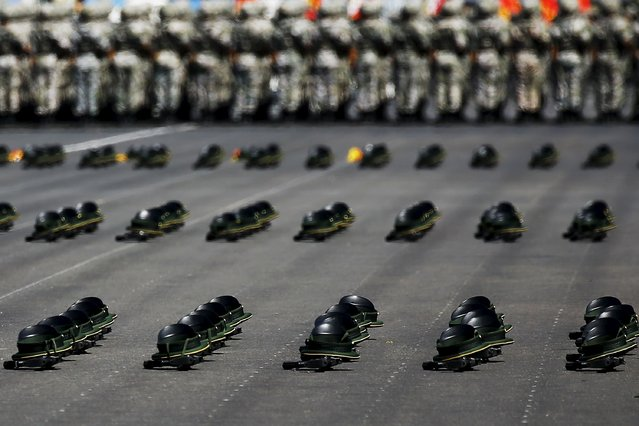 Hats and weapons are seen left on the tarmac as soldiers of China's People's Liberation Army attend a training session for a military parade to mark the 70th anniversary of the end of World War Two, at a military base in Beijing, China, August 22, 2015. (Photo by Damir Sagolj/Reuters)