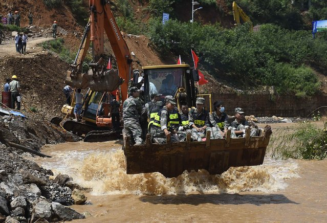 Rescue workers are transported into an earthquake zone on a front loader in Ludian county, Zhaotong, Yunnan province, August 5, 2014. An earthquake in China on the weekend triggered landslides that have blocked rivers and created rapidly growing bodies of water that could unleash more destruction on survivors of the disaster that killed 410 people, state media reported on Thursday. (Photo by Reuters/Stringer)