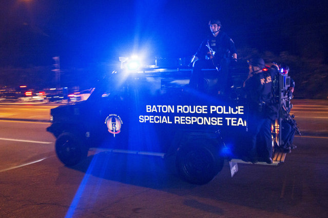 Sheriff Deputies ride outside an armored vehicle on Airline Highway, a major road that passes in front of the Baton Rouge Police Department headquarters, as they attempt to clear protesters from the road in Baton Rouge, La., Saturday, July 9, 2016. People were protesting the shooting death of a black man, Alton Sterling, by two white police officers at a convenience store parking lot last week in Baton Rouge, La. (Photo by Max Becherer/AP Photo)