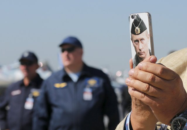 A visitor takes a photograph of a plane with his mobile phone, covered in a phone cover featuring a picture of Russian President Vladimir Putin, at the MAKS International Aviation and Space Salon in Zhukovsky, outside Moscow, Russia, August 25, 2015. (Photo by Maxim Shemetov/Reuters)